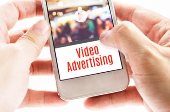 Close up Two hand holding mobile with Video Advertising word Digital business concept.