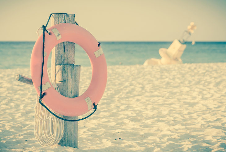 Vintage style photo of life preserver on sandy beach somewhere in Mexico
