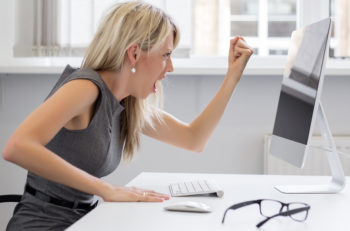 Angry business woman yelling to computer while sitting at desk in office.