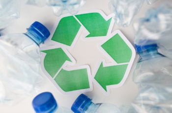 waste recycling, reuse, garbage disposal, environment and ecology concept - close up of used plastic water bottles with green recycle symbol on table