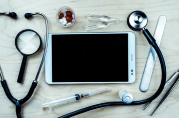Tablet pc with medical objects on a desk as a metaphor for electronic diagnostic or healthcare mobile apps. Medical background