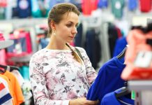 Woman choosing sweater during shopping at garments apparel clothing shop