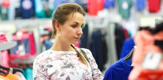 Woman choosing sweater during shopping at garments apparel clothing shop