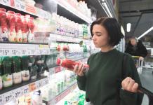 mujer joven viendo etiqueta supermercado