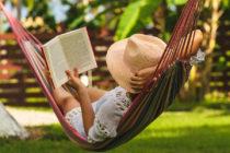Chica lee libro acostada en la hamaca