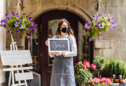 Mujer sostiene letrero de abierto frente a su negocio
